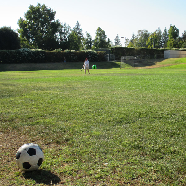 Kathy Spielman watches as her ball races across the field of play.