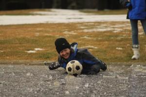 Anita Price crawls across the ice to retrieve her ball.